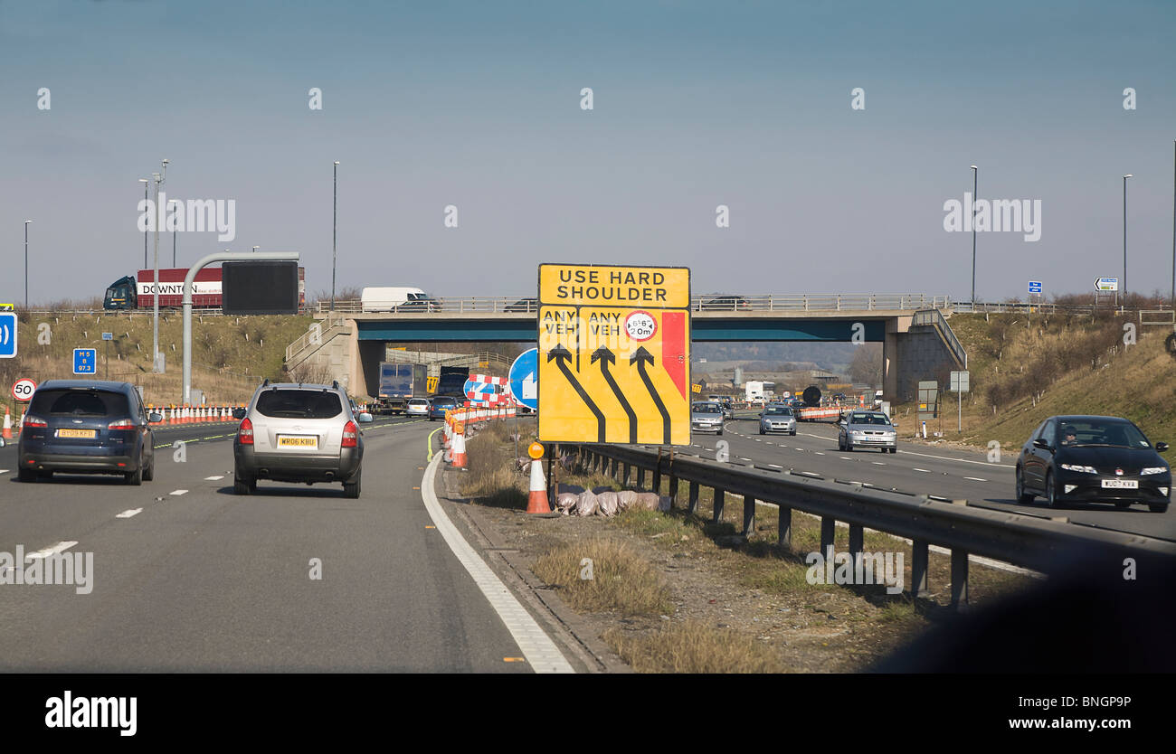 Traffic on motorway with road works sign, England UK - Stock Image