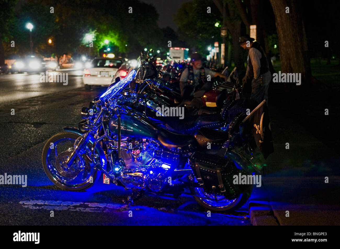 A modified Harley Davidson Motorcycle with lights at night. - Stock Image