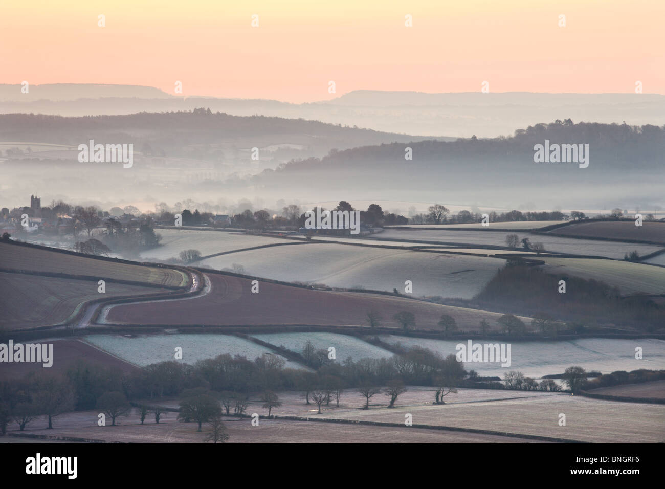 Overlooking frost and mist covered countryside at dawn near the village of Silverton, Devon, England. Winter (March) Stock Photo
