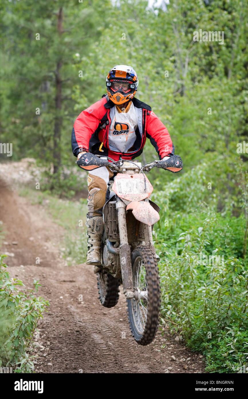 USA, Idaho, Dirt bike rider racing in hills - Stock Image