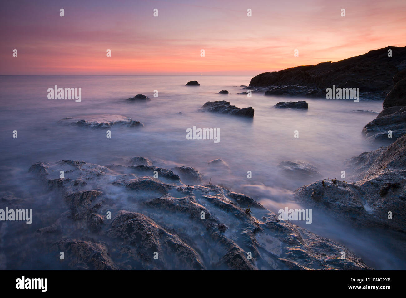 Sunset over the rocky shore of Church Cove, Near Mullion, The Lizard, Cornwall. Spring (April) 2010. - Stock Image