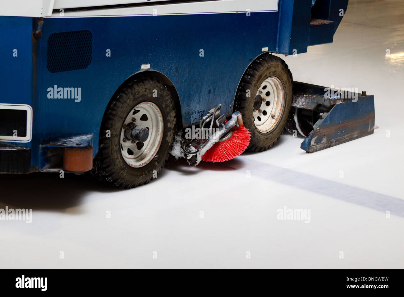 Zamboni Ice Cleaning machine working in hockey arena with ad space - Stock Image