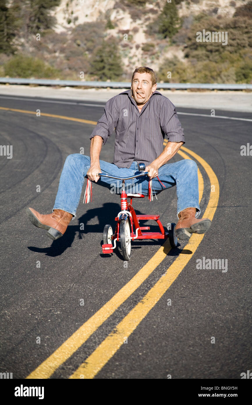 Man acting silly while riding a tricycle - Stock Image