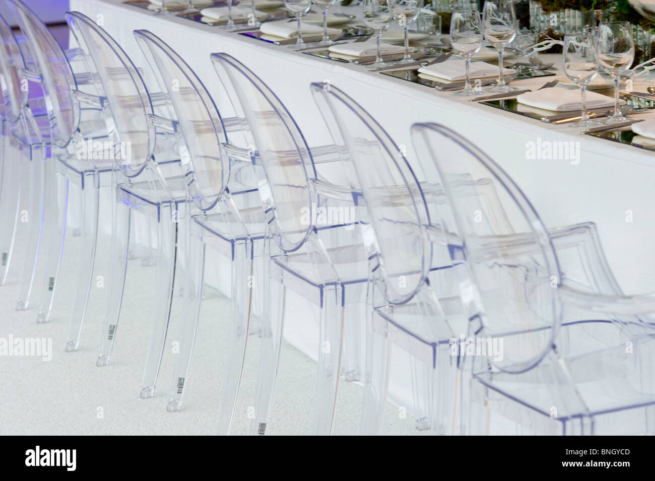 Lucite chairs at dinner party set up - Stock Image