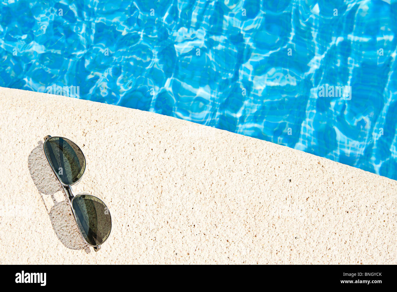 Shot of Sunglasses next to the Swimming Pool - Stock Image