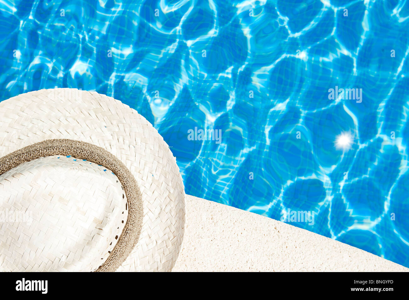 Shot of a Sunhat next to the Swimming Pool Stock Photo