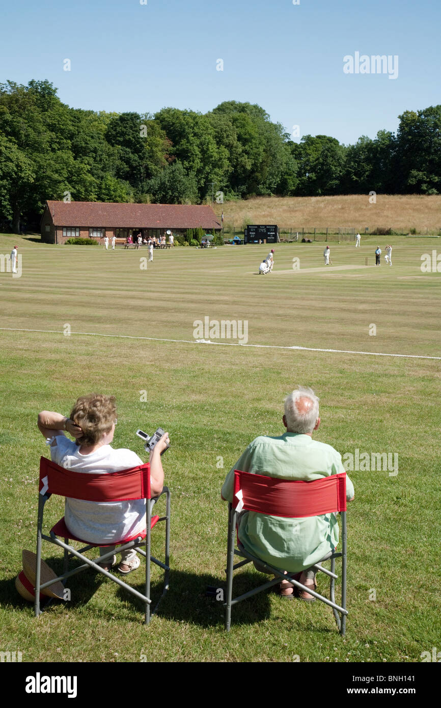A couple watching a game of village cricket in the village of Lyminge near Folkestone, Kent, UK Stock Photo