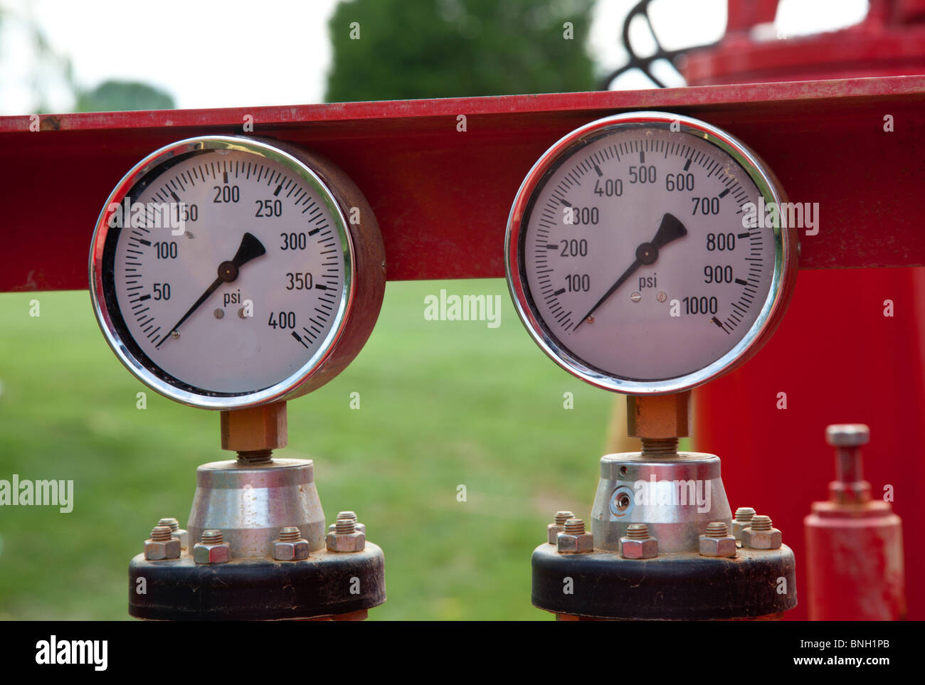 Two similar pressure gauges on heavy equipment - Stock Image