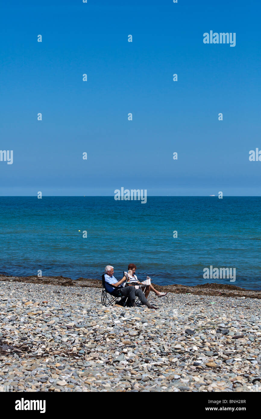 couple reading newspapers on deserted beach at  summer in Bray, near Dublin, Ireland - Stock Image
