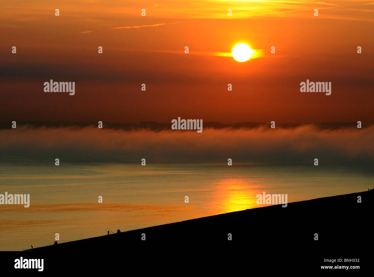 Heat wave and fog bank with sunsetting over Lyme Bay, viewed from Chesil beach. Dorset UK. Stock Photo