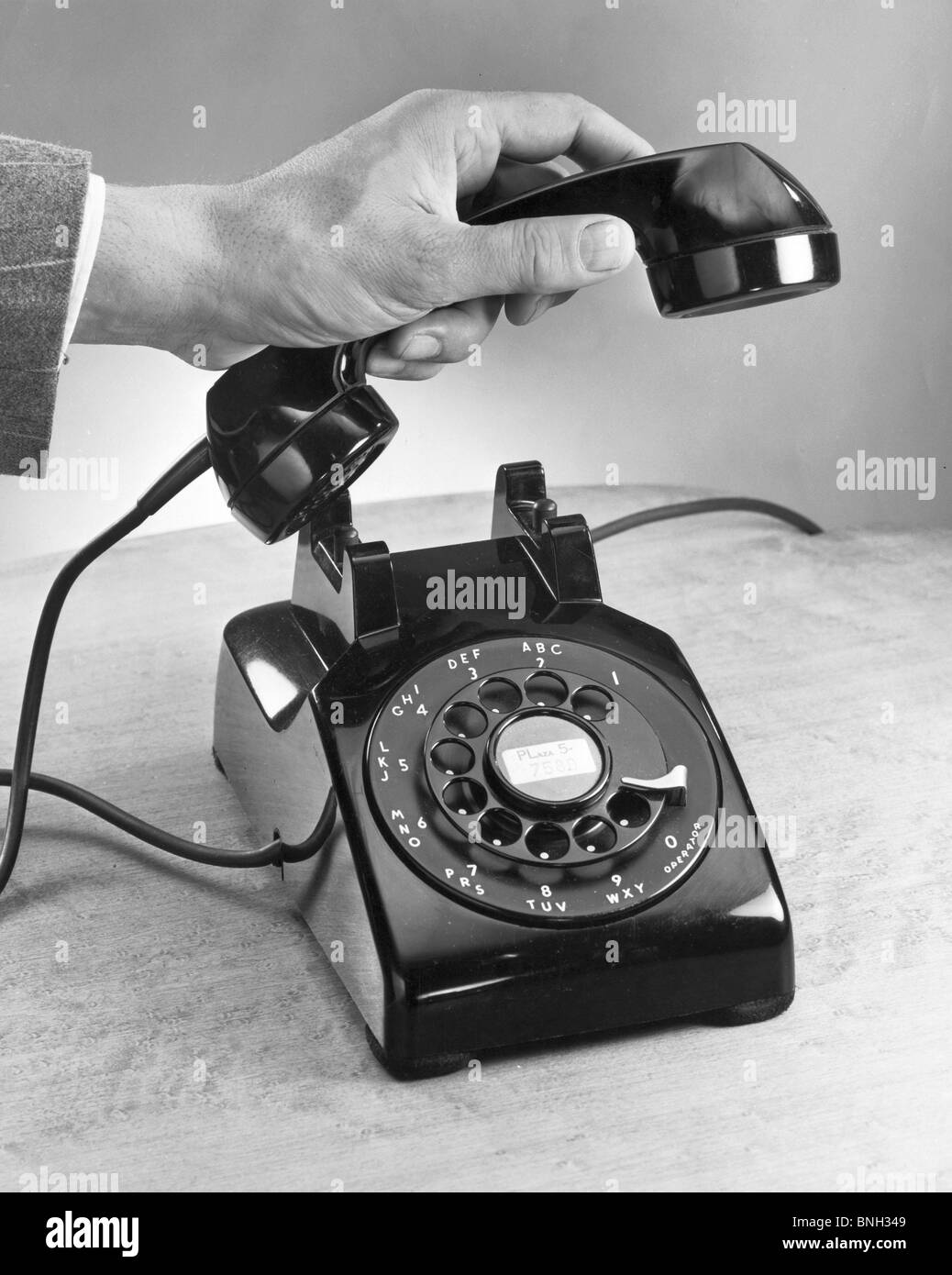 Close-up of a man's hand holding a telephone receiver - Stock Image