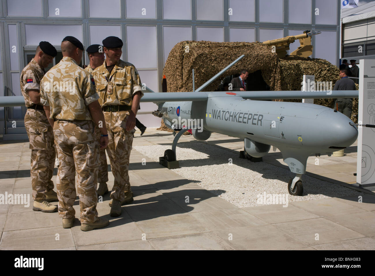British Army soldiers gather outside the hospitality chalet of aerospace manufacturer Thales. - Stock Image