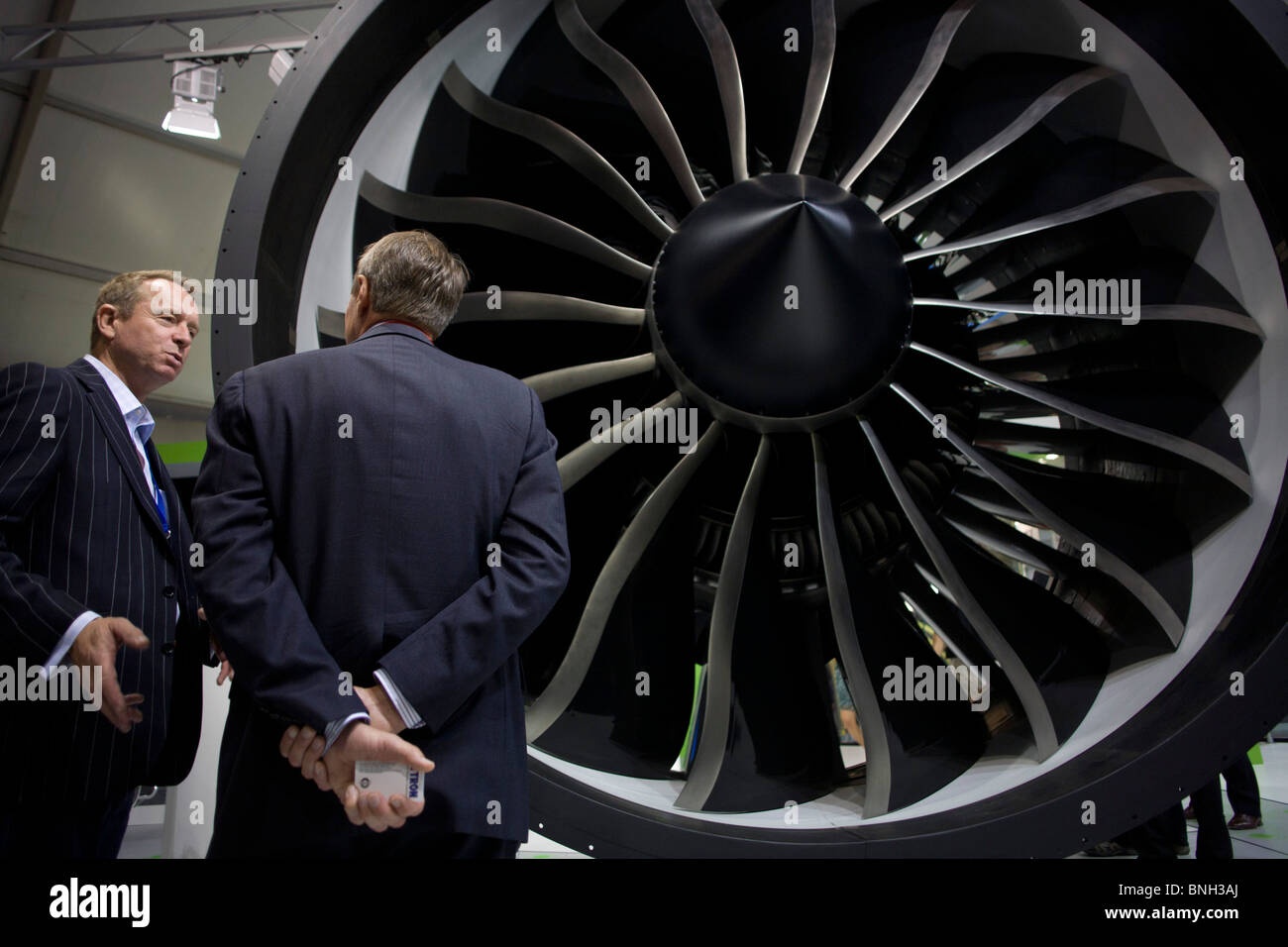An employee and potential buyer discuss potential business deals at the General Electric (GE) exhibition stand. - Stock Image