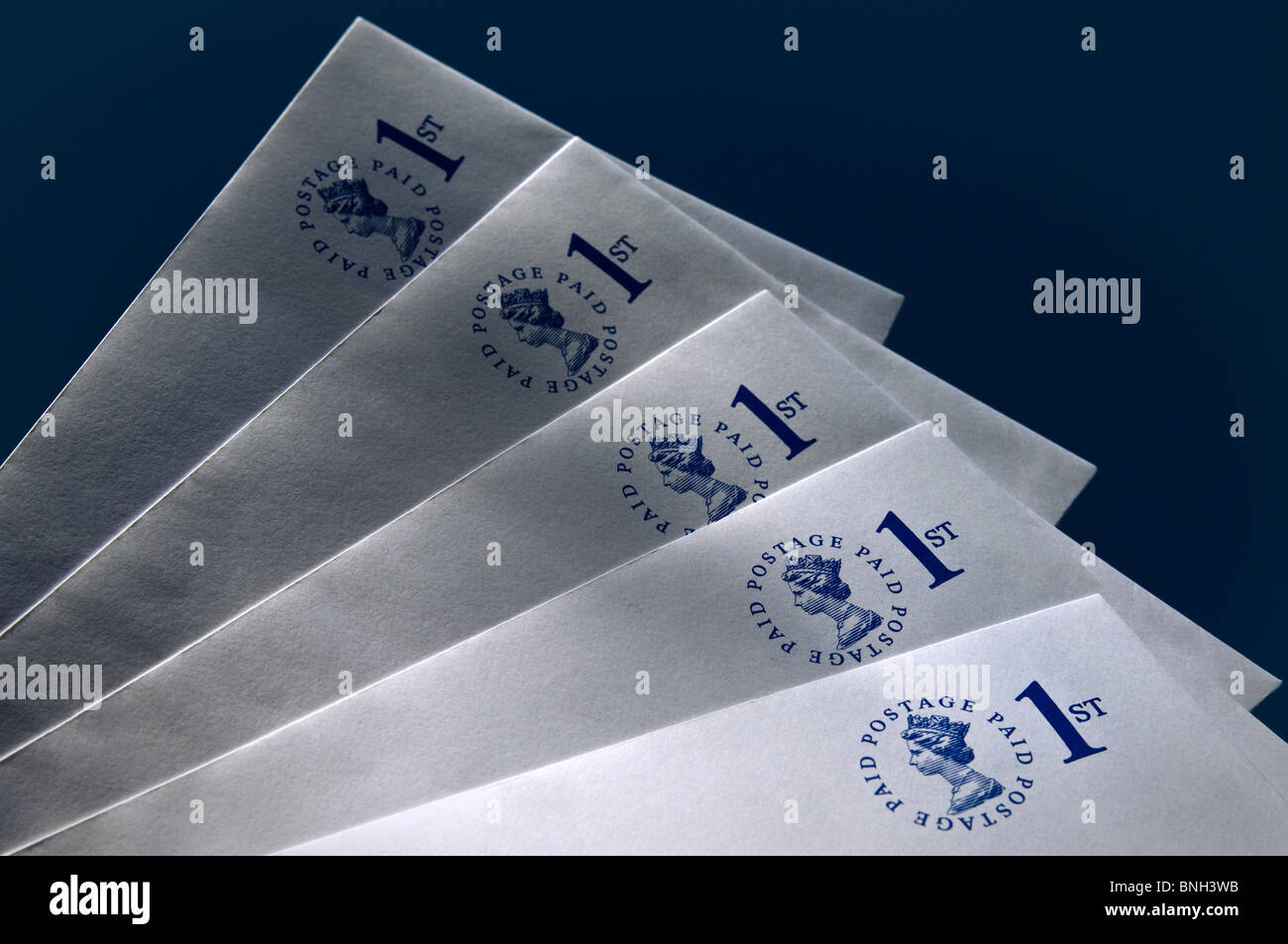 Pre-paid UK first class envelopes on dark blue background - Stock Image