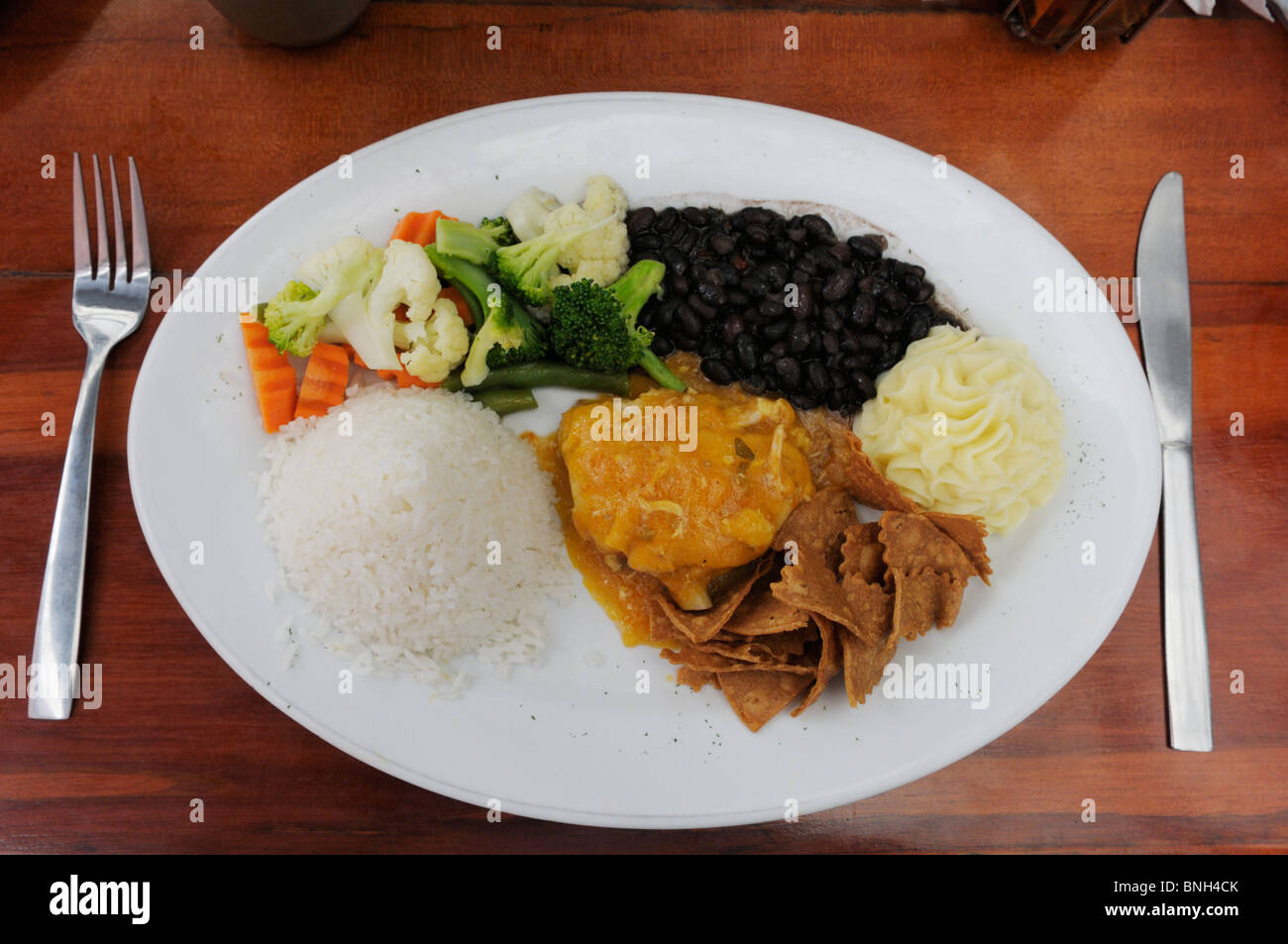 Typical Costa Rican meal, comida tipica.  Meat (chicken), vegetable, rice and beans (gallo pinto).  Restaurant in - Stock Image