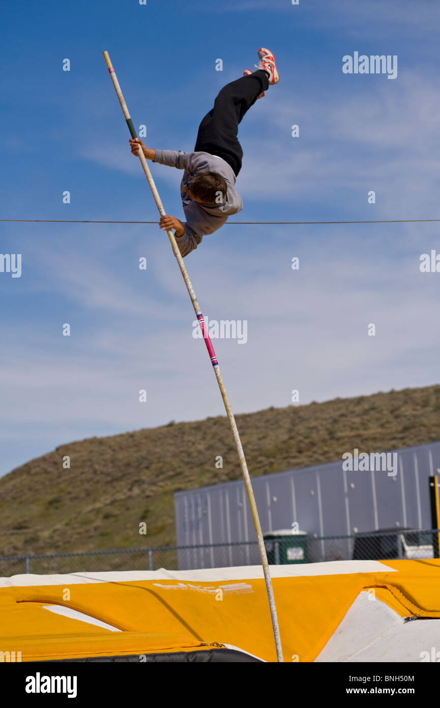 high school pole vaulter clearing the wire - Stock Image