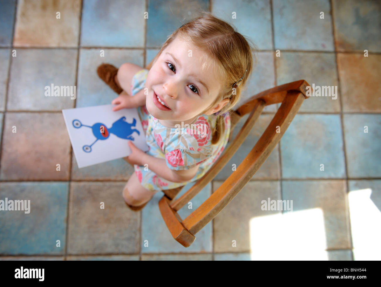 A three year old girl with a picture of the alien character Bic who is used in a test for specific language impairments Stock Photo