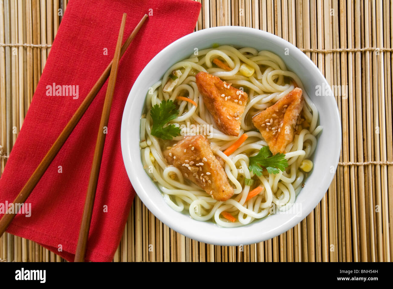 Udon noodle soup with fried tofu and sesame seeds on top Stock Photo
