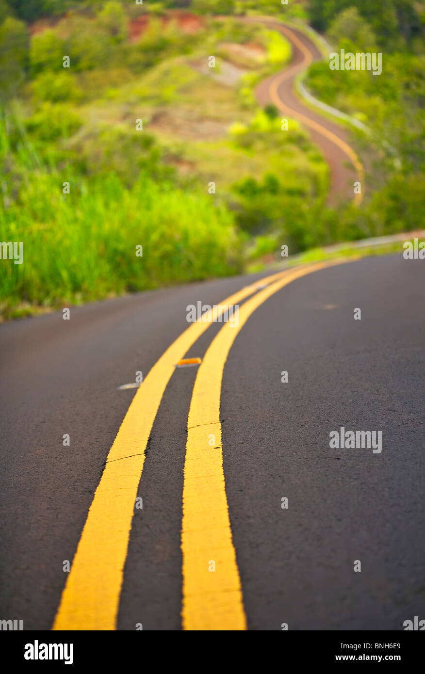 Long winding road traveling up a hillside - Stock Image