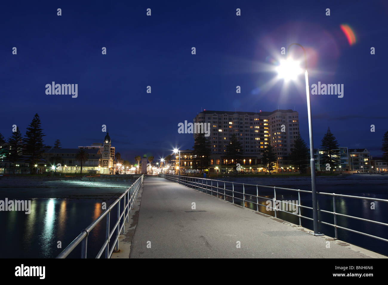 A light shines on the Glenelg Jetty in Adelaide, South Australia, just after sunset. - Stock Image