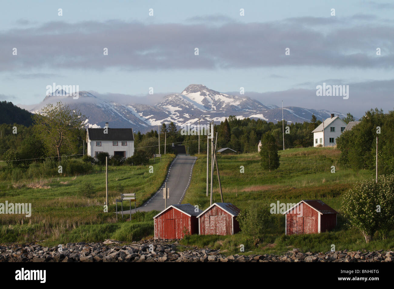 Fisher huts (rorbus) at the harbour of Styrkesnes, Nordland Fylke, Norway. Snow-covered mountains are in the background. Stock Photo