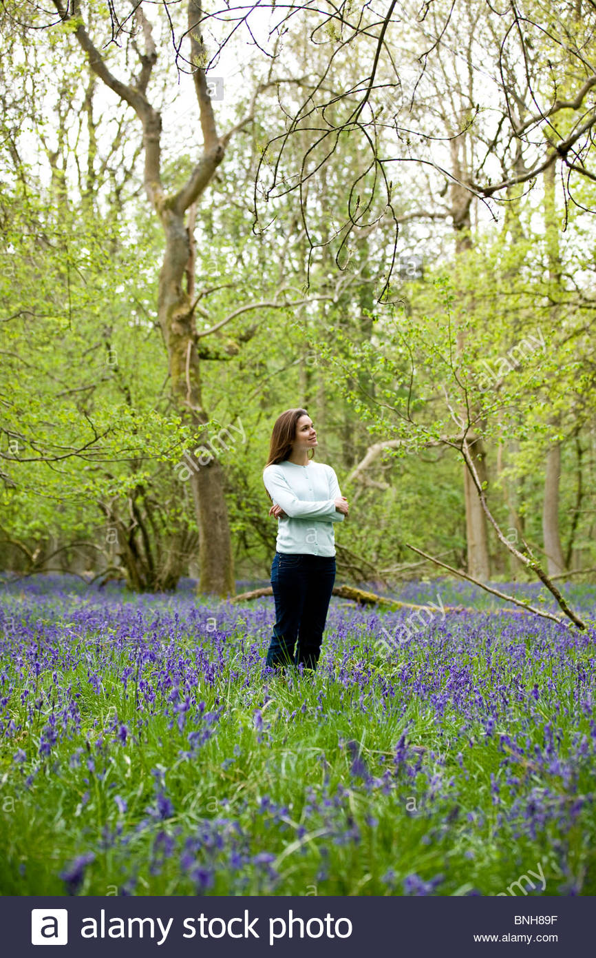 A young woman standing in a bluebell wood - Stock Image