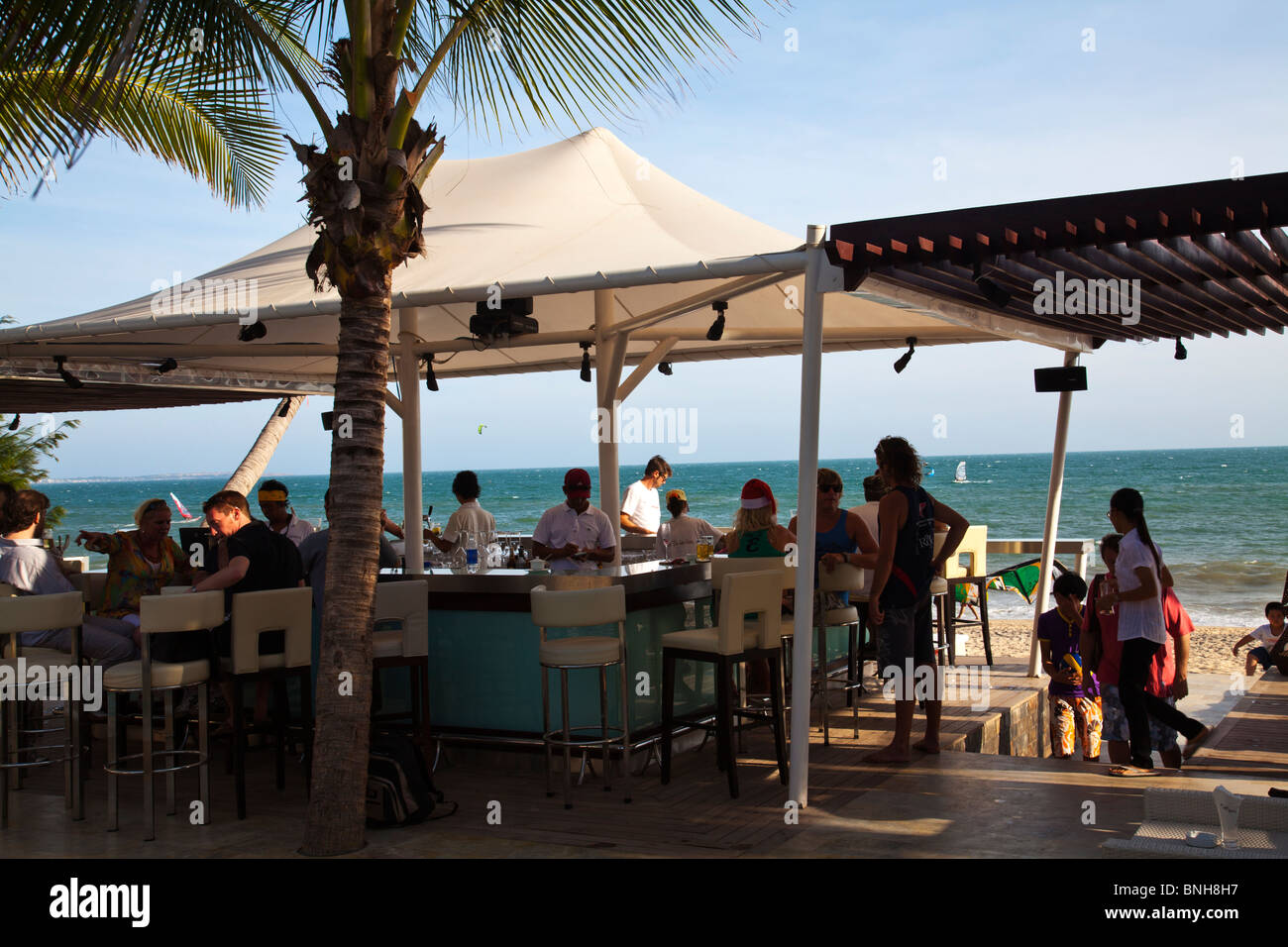 Travellers at bar at hot spot beach bar Shankara and view of sea and windsurfers - Stock Image