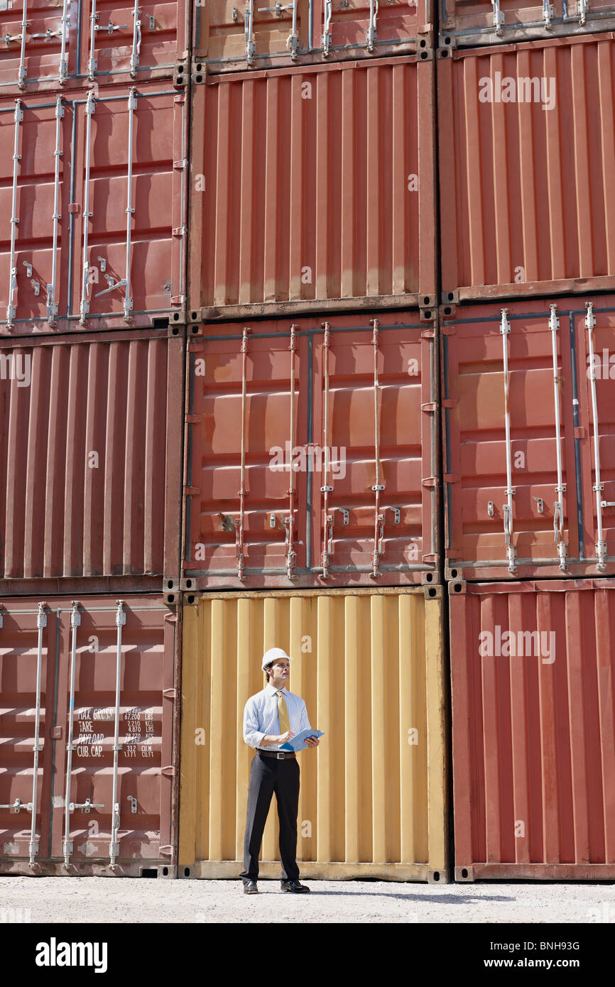 mid adult businessman standing near cargo container and looking up. Vertical shape, copy space - Stock Image