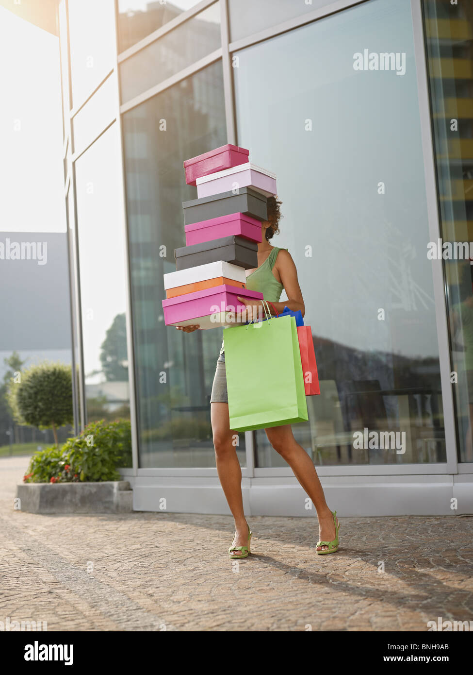 hispanic woman balancing stack of shoe boxes out of shopping center. Vertical shape, full length, copy space - Stock Image