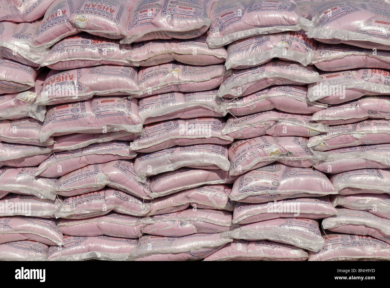 Food Feeding auxiliary goods piles large amounts of rice bags emirate Sharjah Arabia Arabic Dubai eating trade commerce - Stock Image