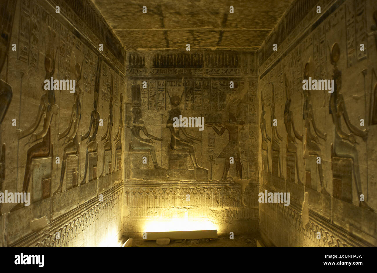Ptolemaic temple of Hathor and Maat. Polychrome reliefs that decorate the interior. Seated gods. Deir el-Medina. - Stock Image