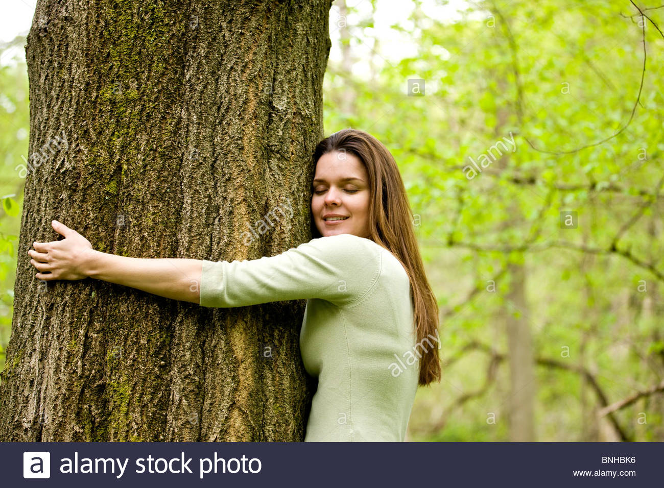 A young woman hugging a tree - Stock Image