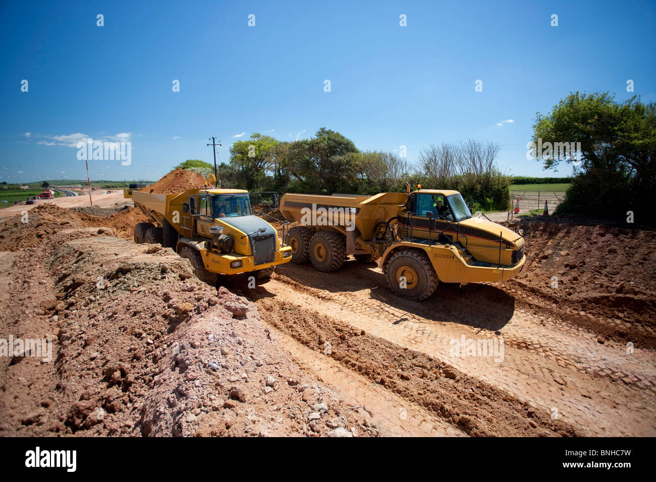 Articulated earth movers on road construction site. - Stock Image