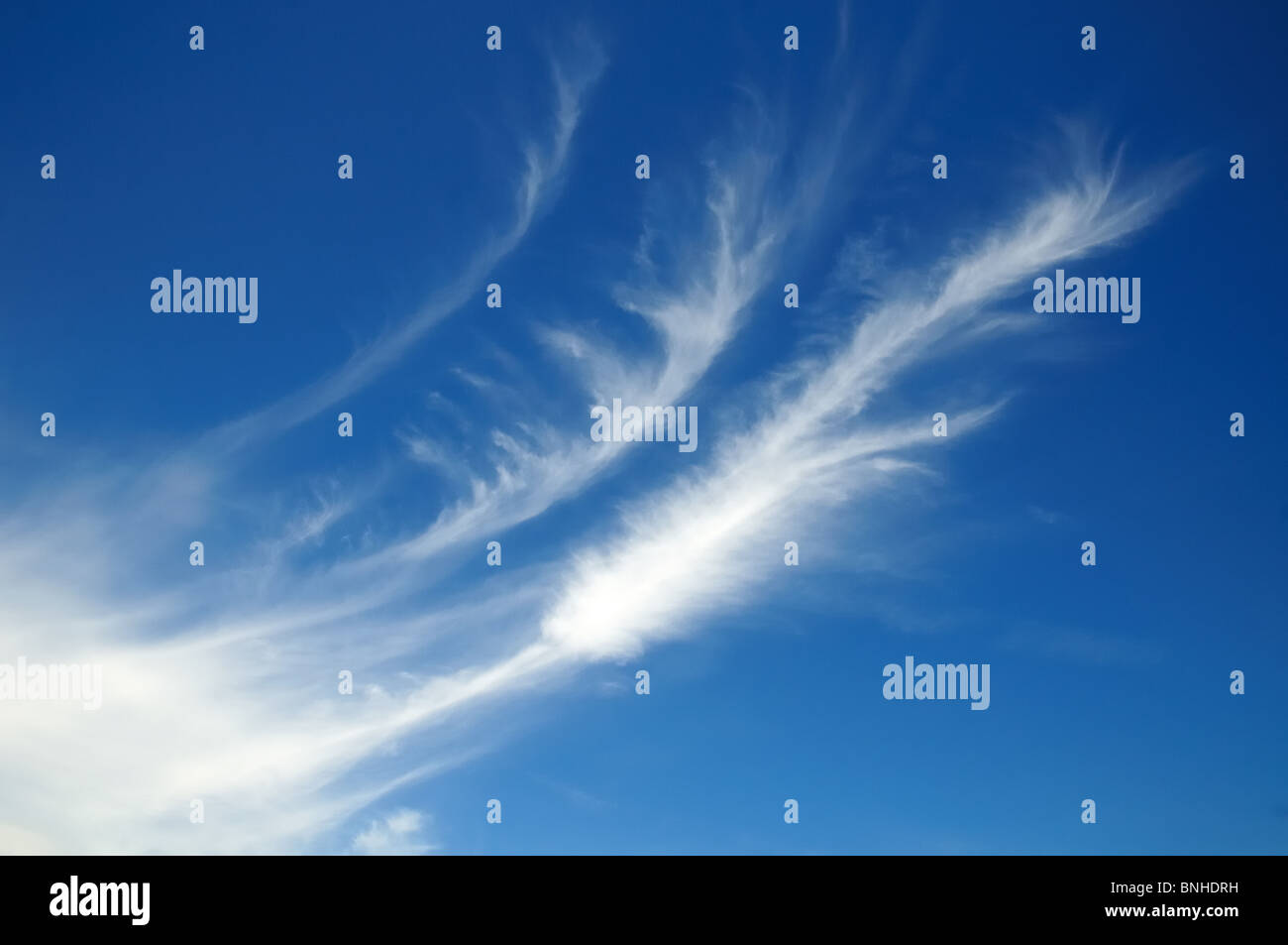 White cloud patterns against blue sky - Stock Image