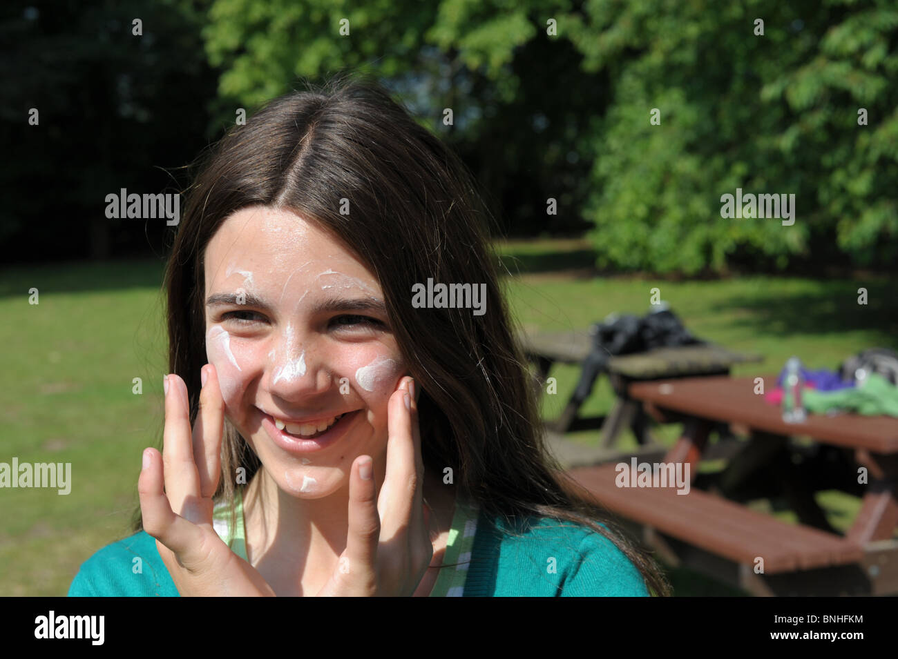 Girl happily applying suncream to protect her face from sunburn in a park on a hot sunny day - Stock Image