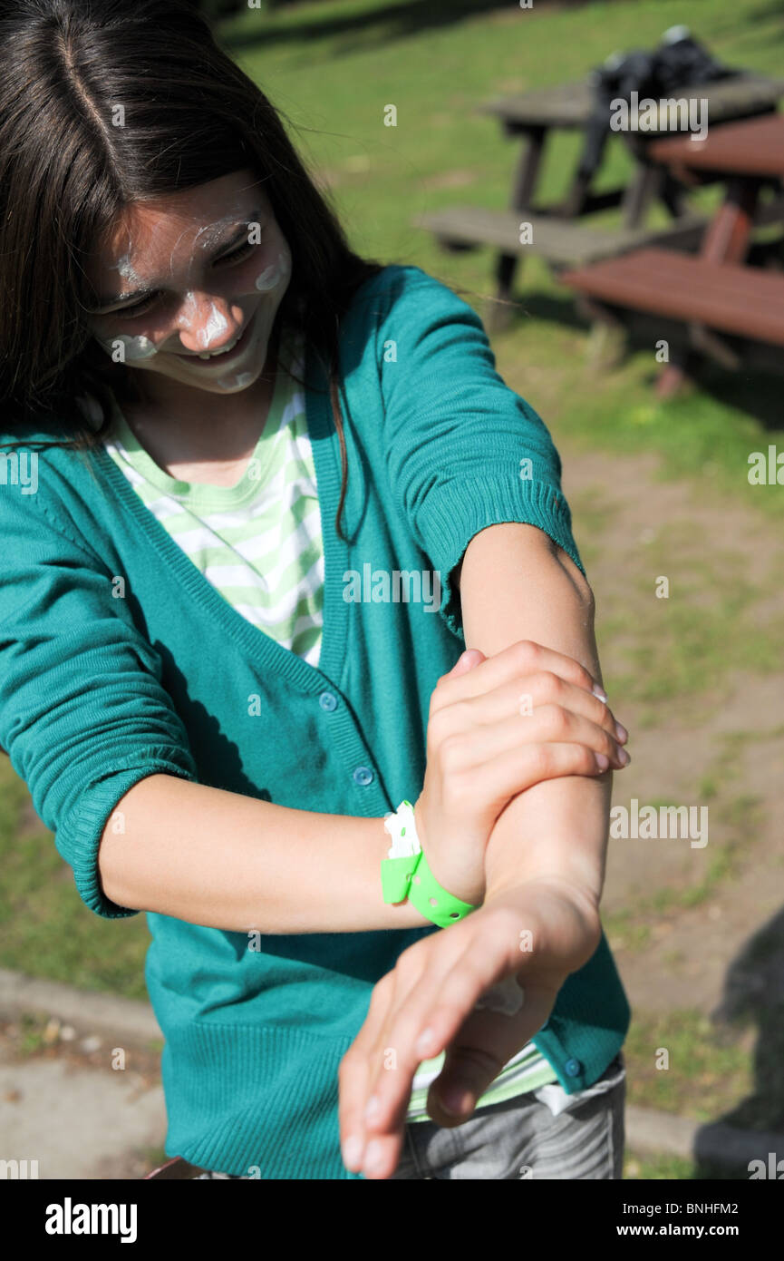 Girl happily rubs suncream to protect her face and arms from sunburn in a park on a hot sunny day - Stock Image