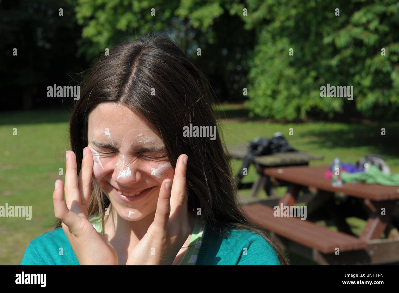 Girl unhappy about putting suncream on her face in a park on  a hot sunny day - Stock Image