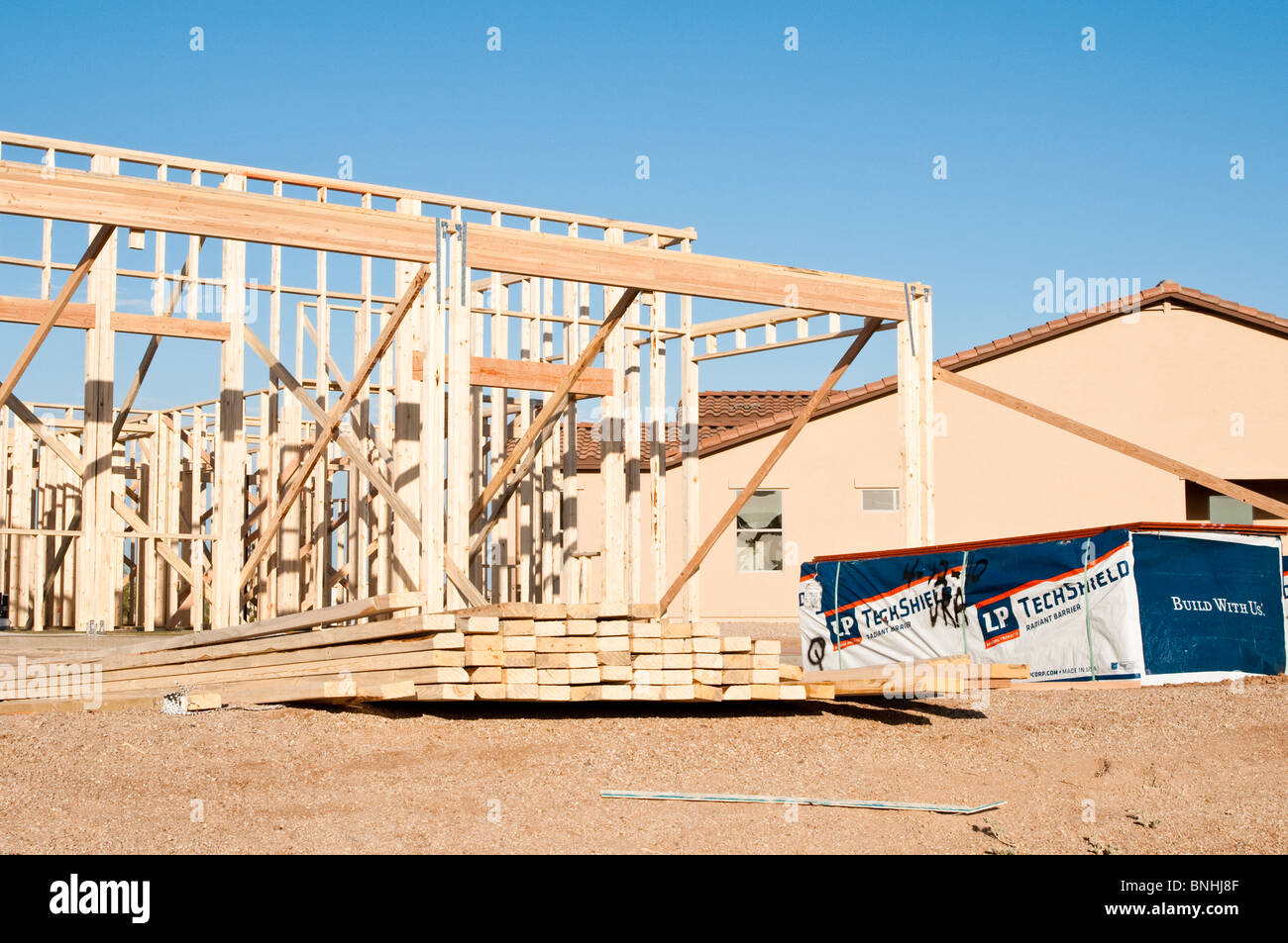 Building materials are stacked on the construction site for a new wood frame house beign built in Arizona. - Stock Image