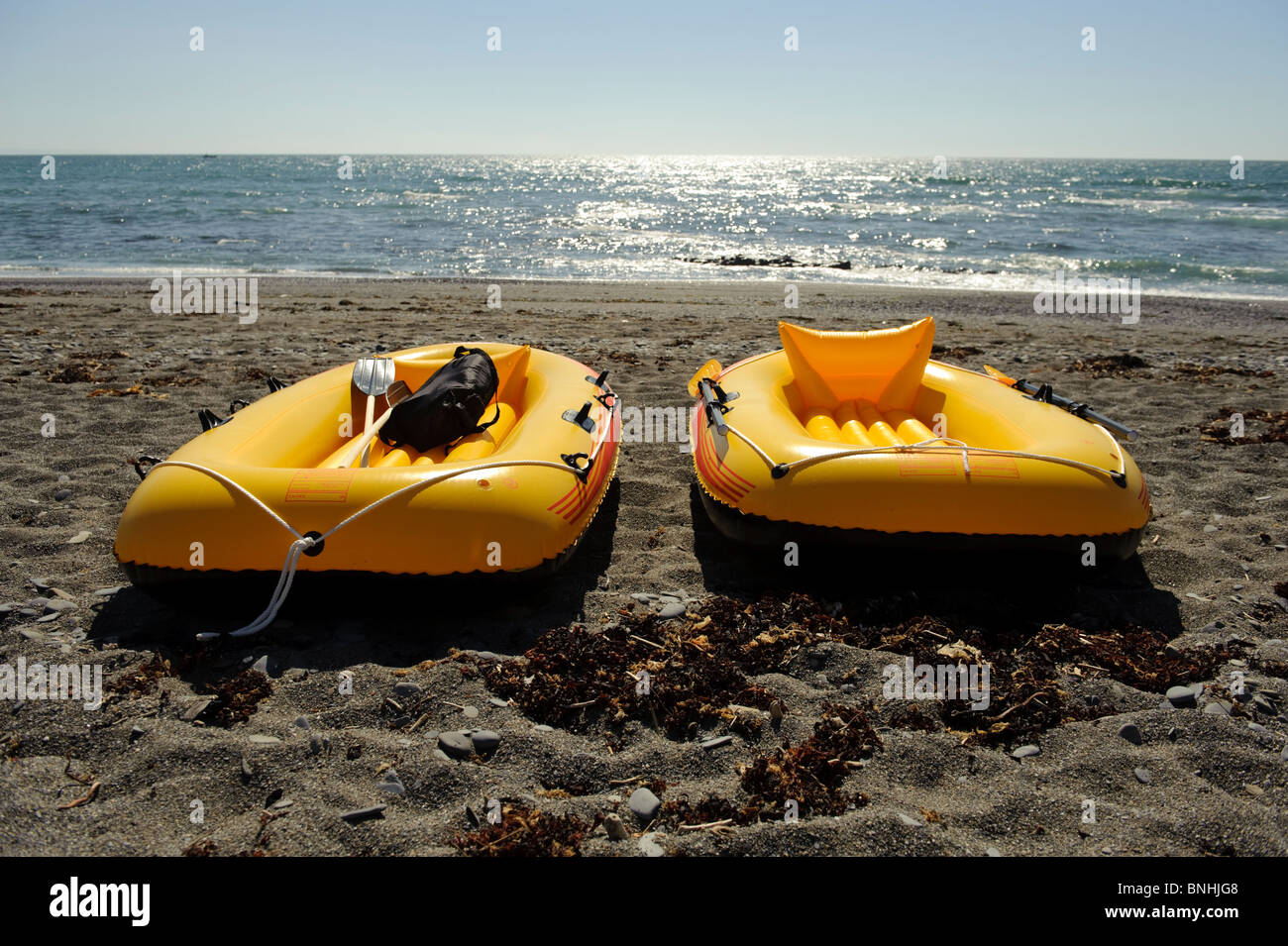 Two yellow inflatable dinghies on a beach, summer afternoon, aberystwyth wales UK - Stock Image