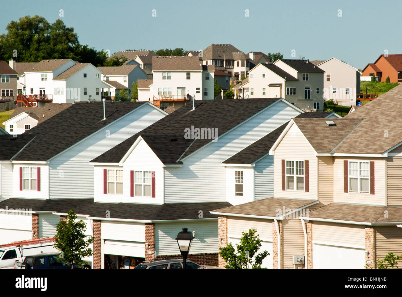 View of multiple family residences in a suburban neighborhood. Single family homes are seen in the background. - Stock Image