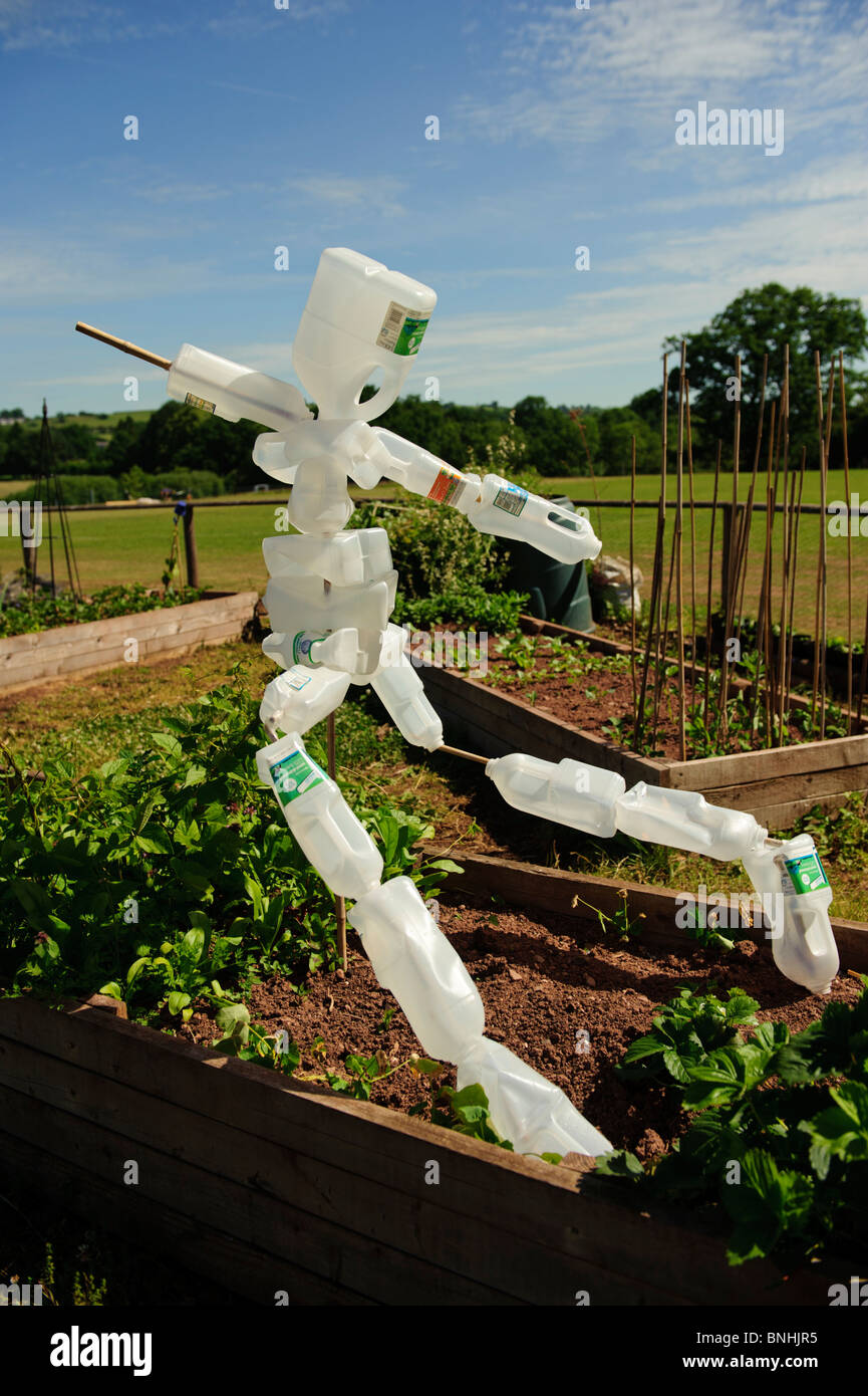 A scarecrow made from recycled plastic milk bottles in a primary school garden, Wales UK - Stock Image