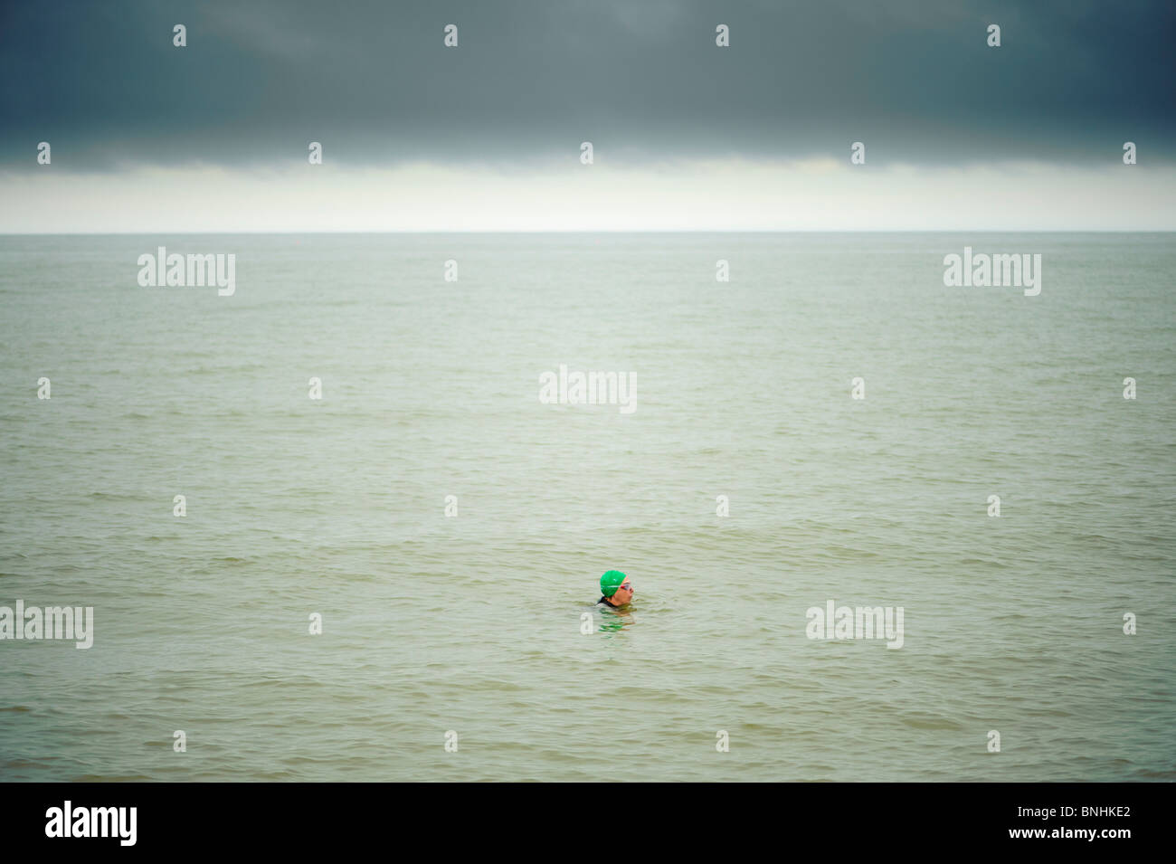 A person swimming alone in the sea in Aberystwyth on a grey overcast cloudy summer afternoon, july 2010, UK - Stock Image