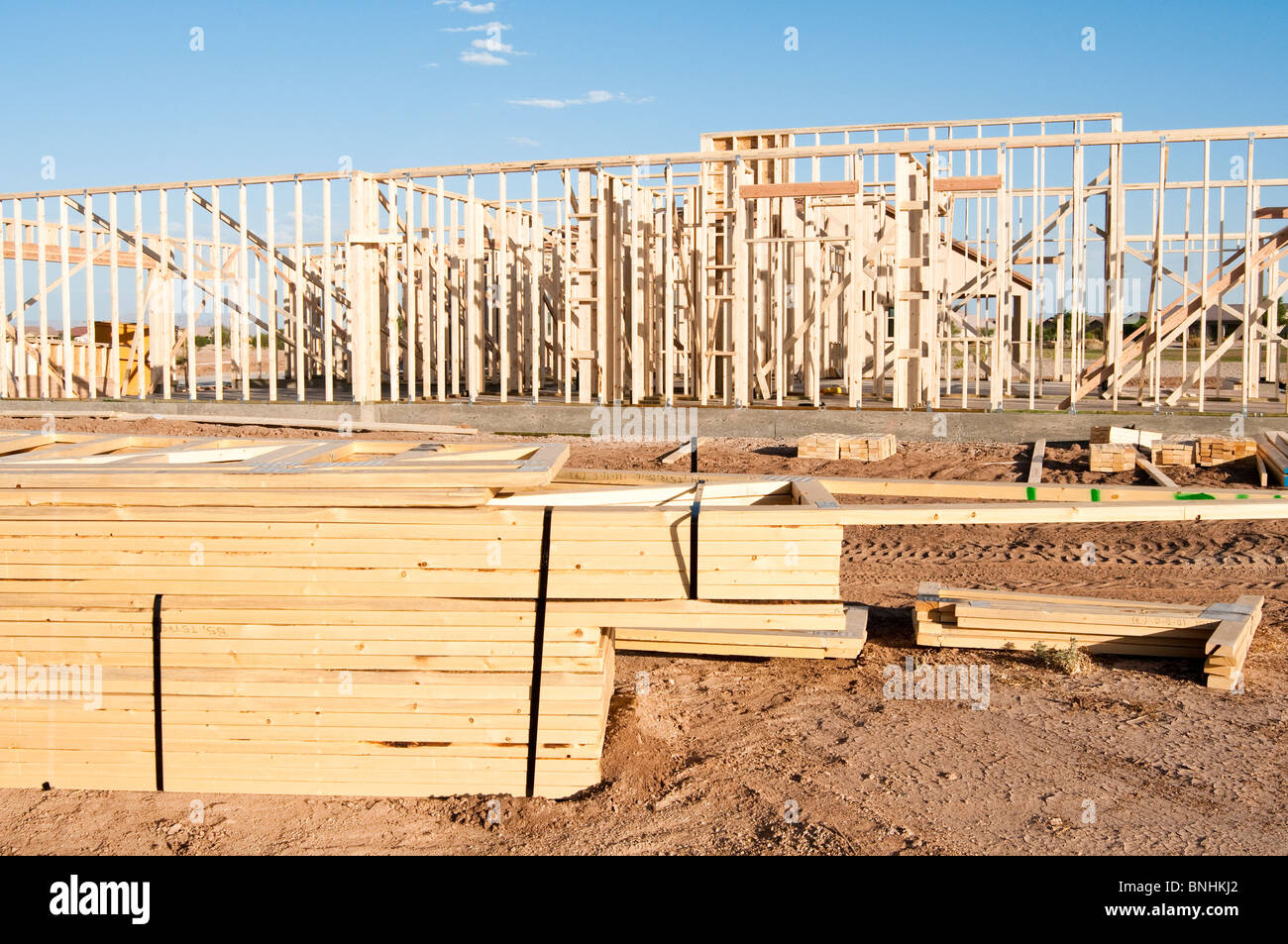 Building materials are stacked on the construction site for a new wood frame house being built in Arizona. - Stock Image