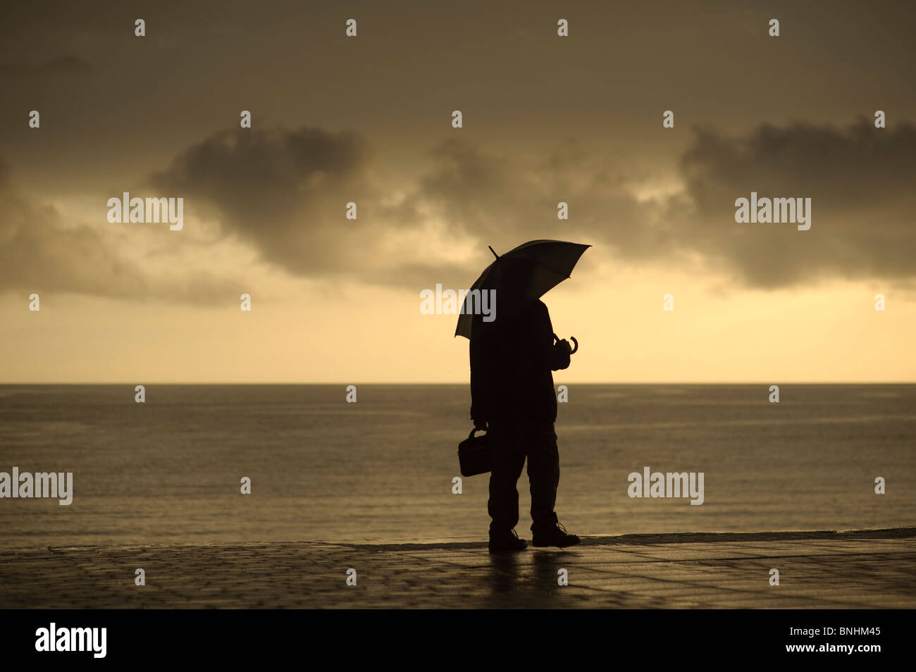 A man sheltering under an umbrella on a wet summer evening, Aberystwyth Wales UK - Stock Image
