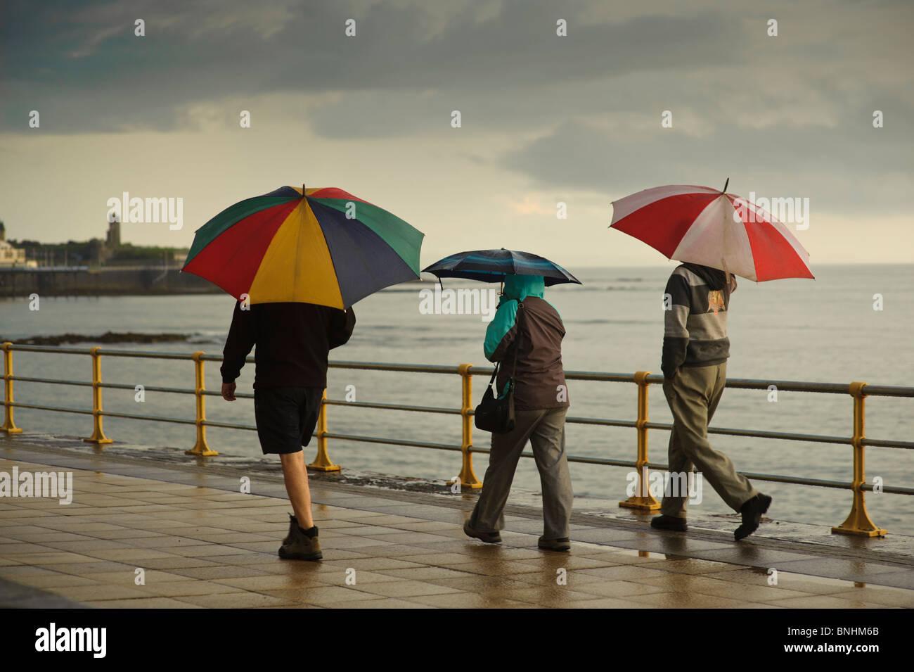 Three people sheltering under umbrellas on a wet summer evening, Aberystwyth Wales UK - Stock Image