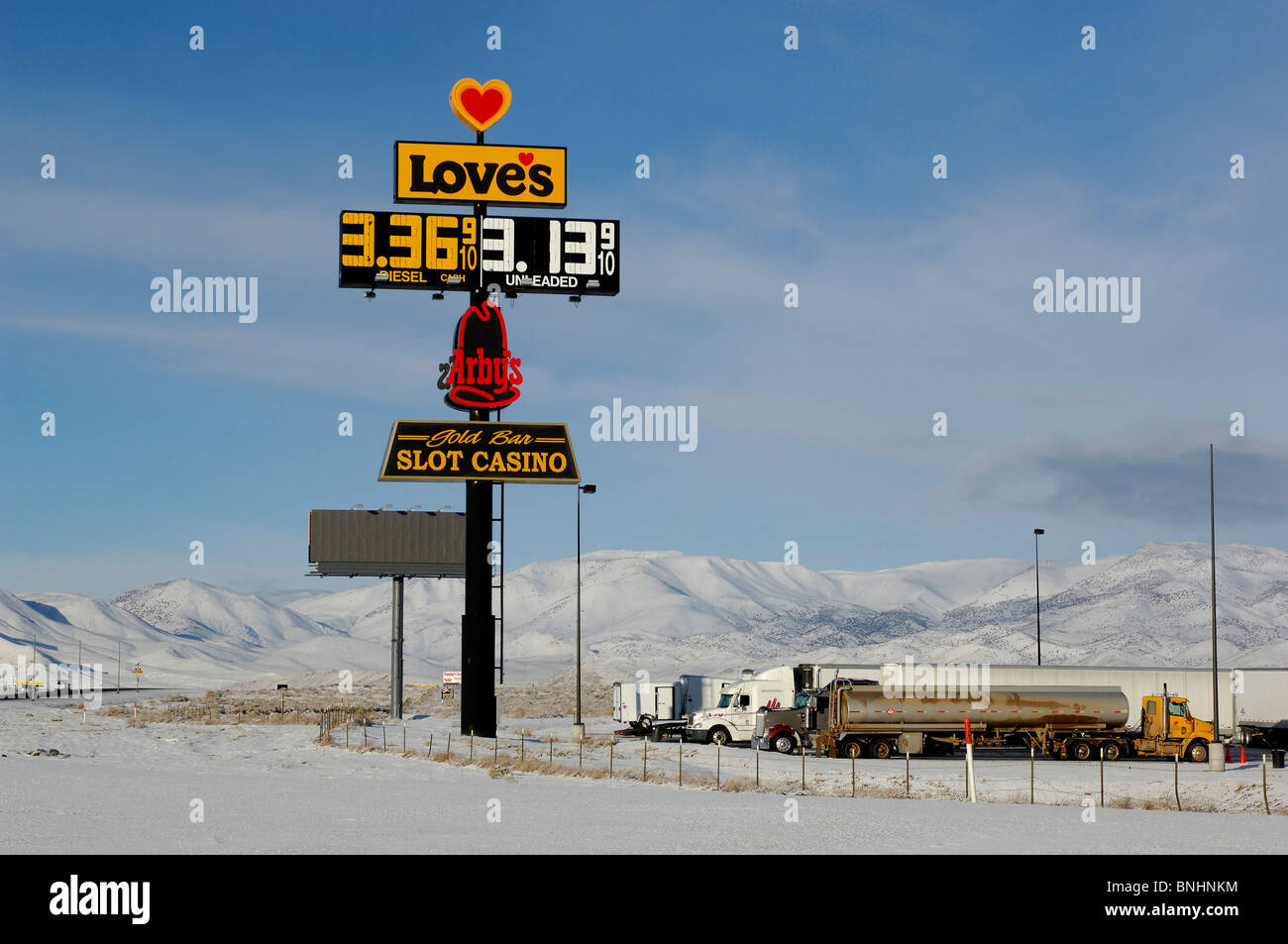 USA Loves Truck Stop near Reno Nevada winter snow trucks filling gas station garage sign parking lot highway country - Stock Image