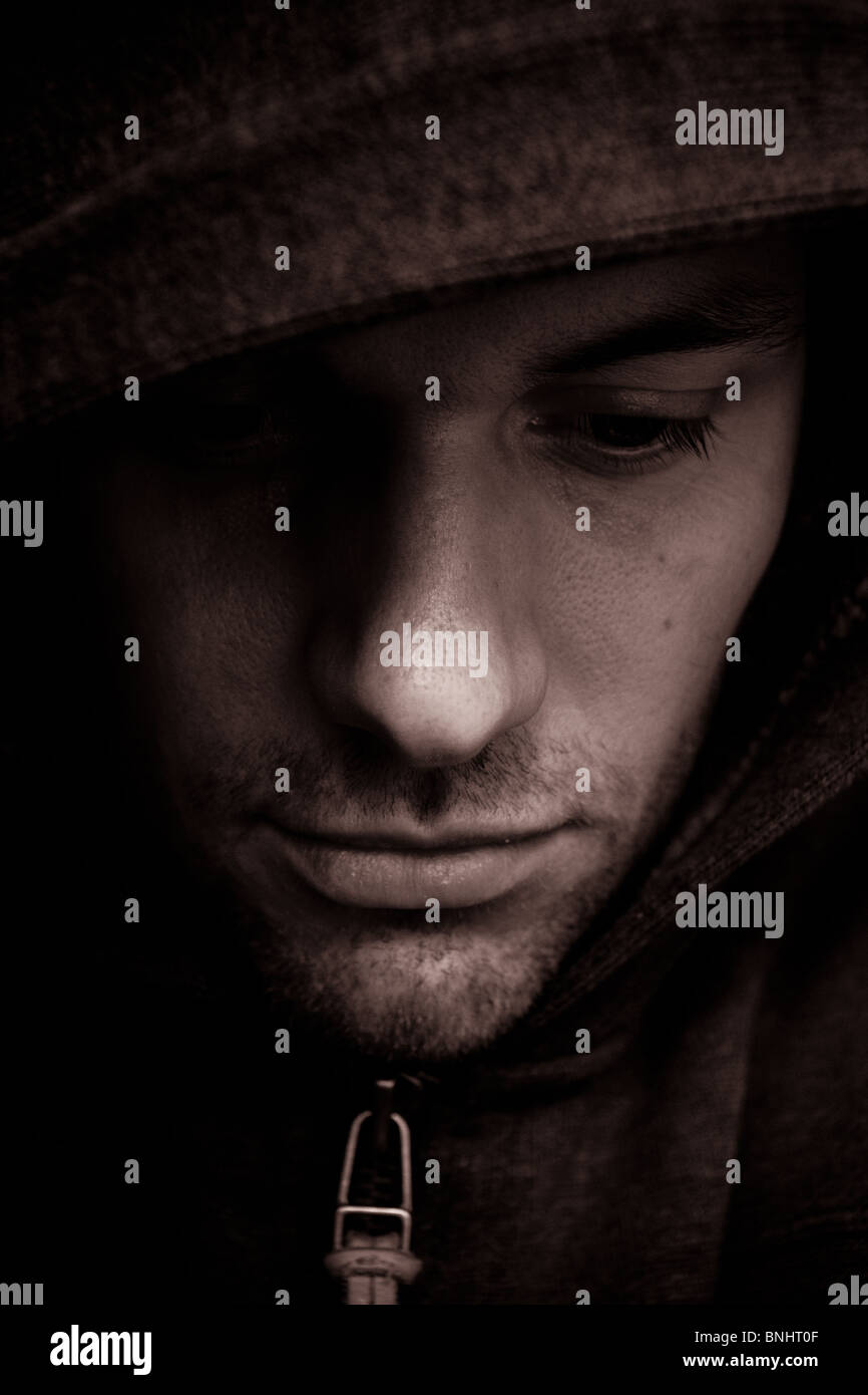Self portrait.  Man looking sad/depressed wearing a 'hoodie' to partially obscure his face.  Coverted to - Stock Image