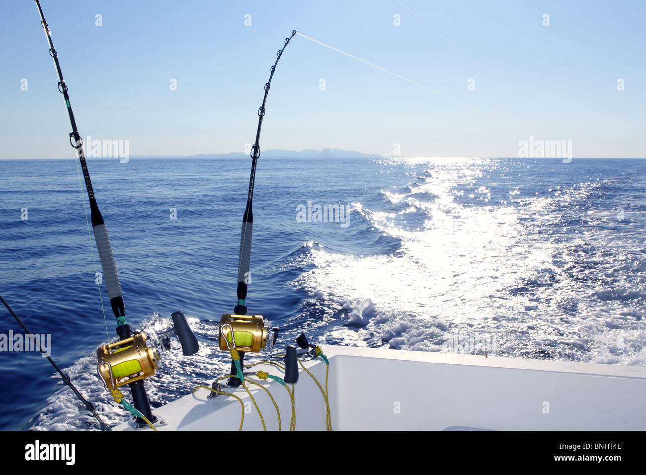 Trolling offshore fisherboat rod reels wake sea reflection horizon - Stock Image