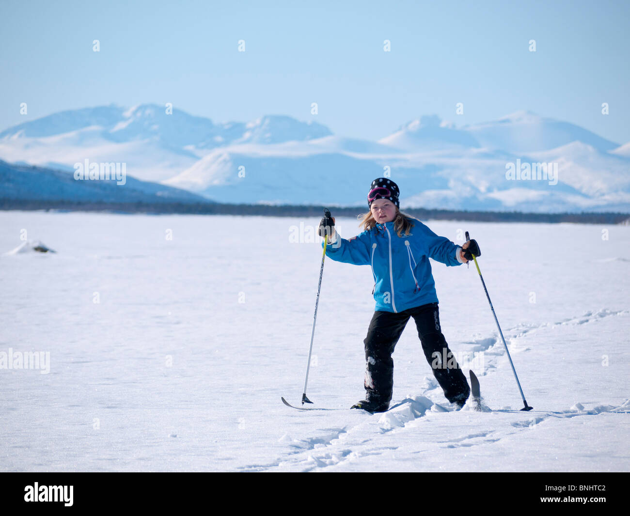 An eight year old skiing girl makes her way above the frozen Kaalasjärvi lake in front of the Kebnekaise massif - Stock Image