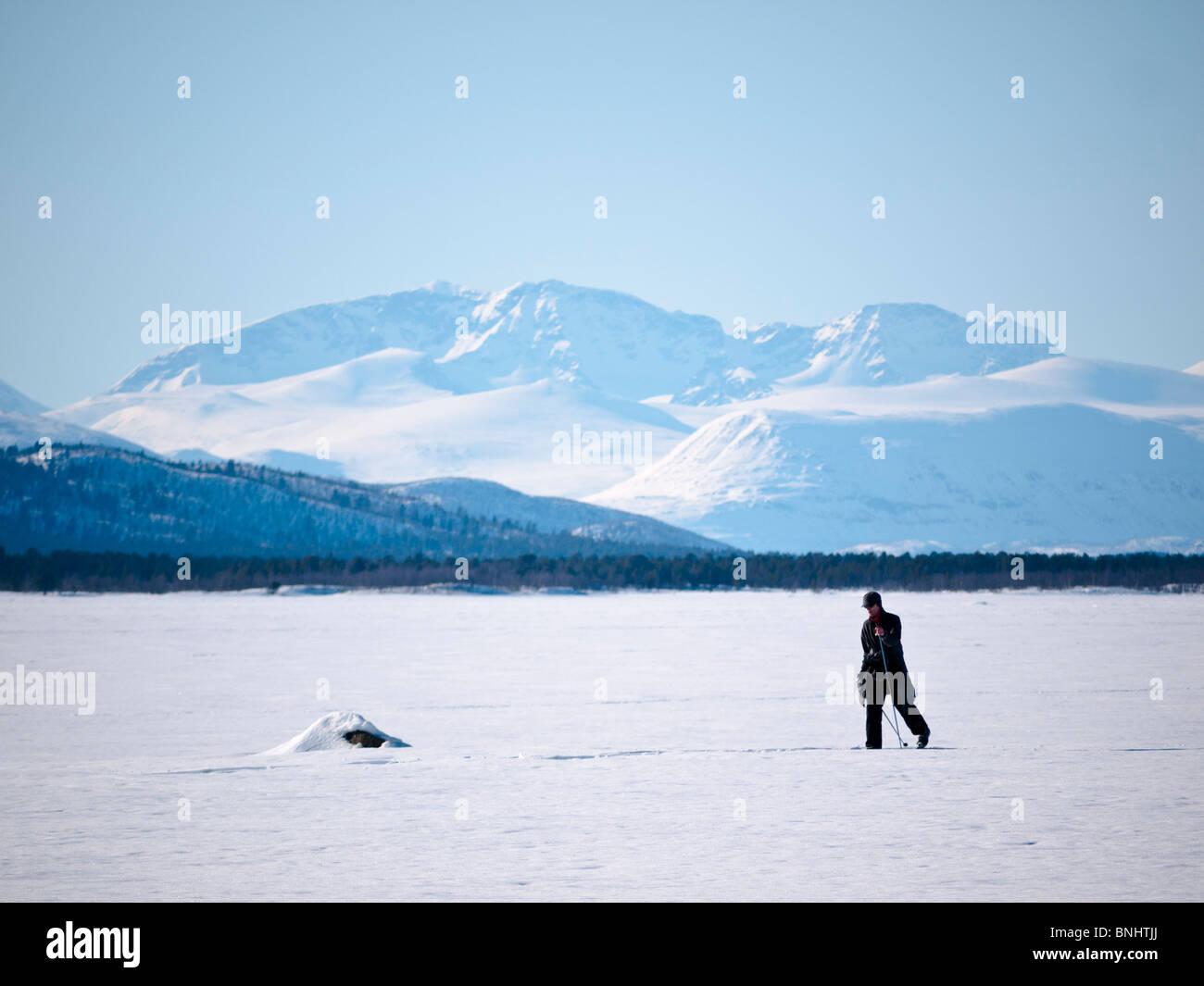 A skier makes his way above the frozen Kaalasjärvi lake in front of the Kebnekaise massif in Kiruna, Lapland, - Stock Image